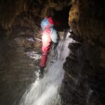 Scrambling down the waterfall in Swildon's Hole cave, the Mendips